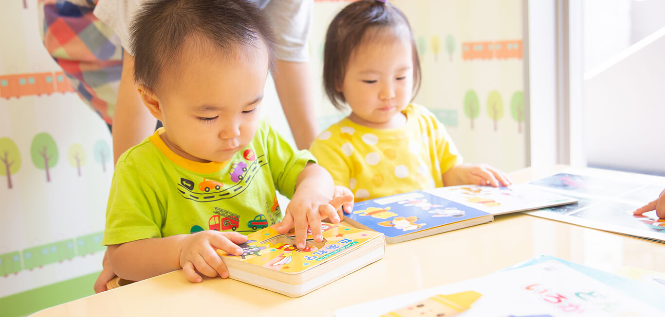 園児2名が真剣に絵本を読んでいる様子