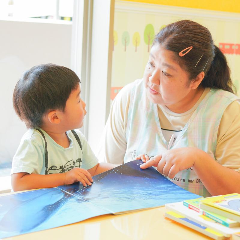 先生と男の子が目を合わせながら絵本を読む様子