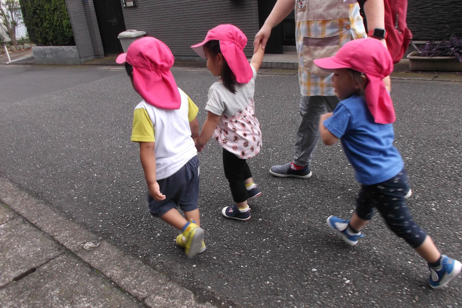 先生と園児たちが手をつないでお散歩する後ろ姿